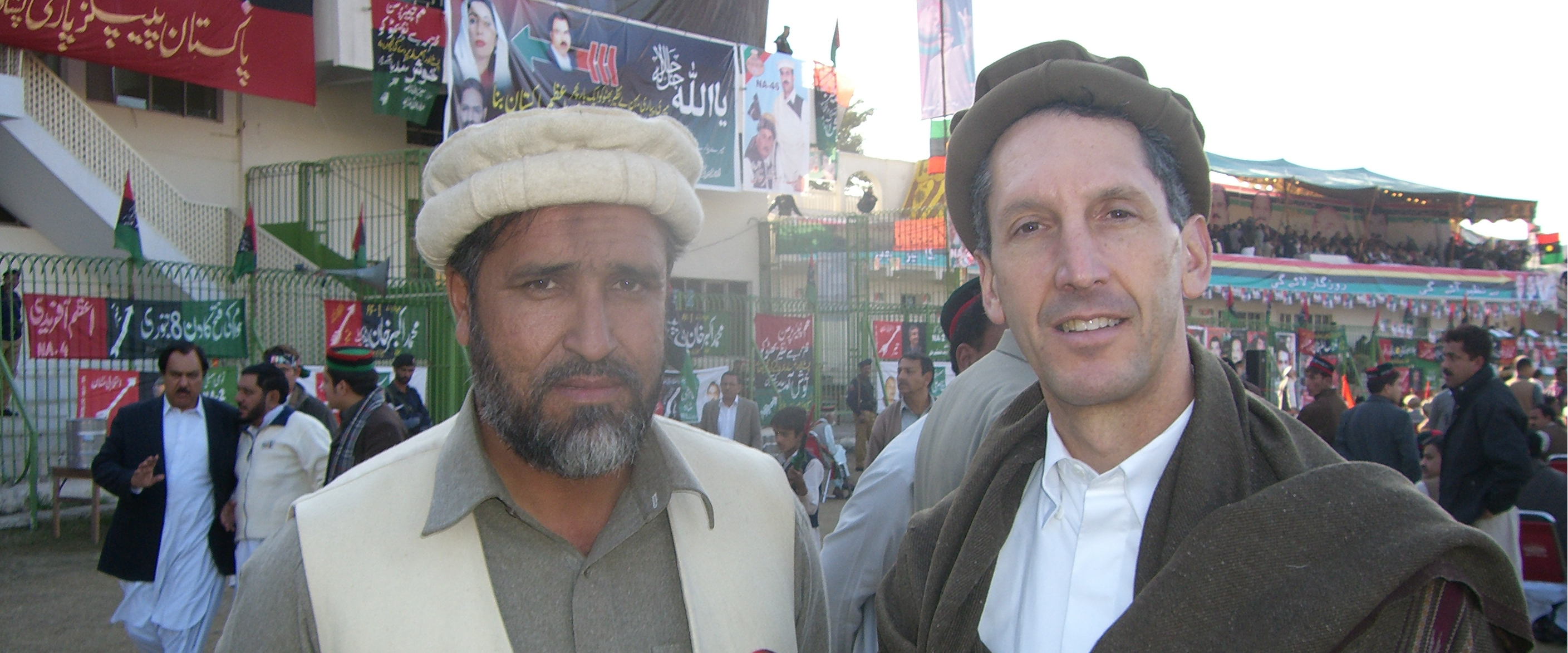 Edward P. Joseph in Peshawar in local Pashtun garb (recommended for security), attending Benazir Bhutto's election rally at the local cricket stadium, on 26 December 2007. Bhutto supporter is pictured alongside.