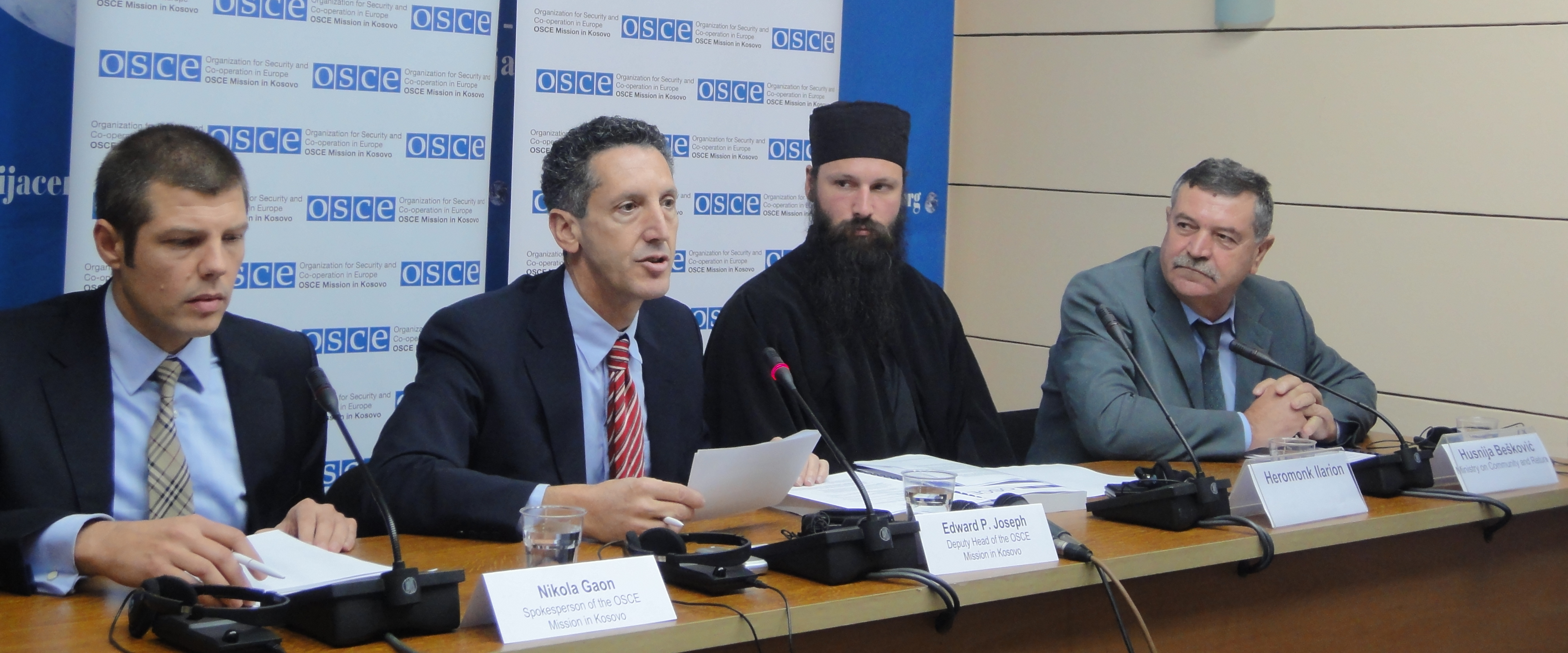 Deputy Head of OSCE Mission (Edward P. Joseph) seated next to Serbian Orthodox priest at the release of OSCE's report on the condition of Serb graveyards in Kosovo.